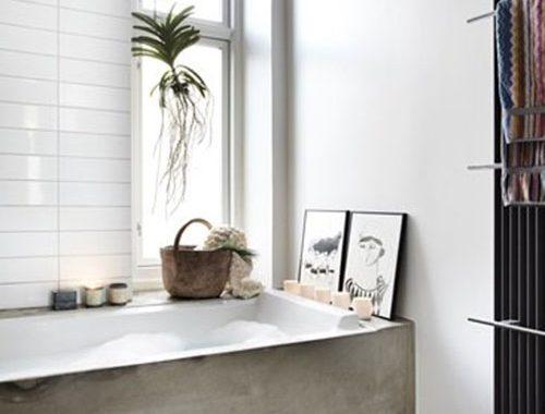 Badkamer met betonnen vloer en bad