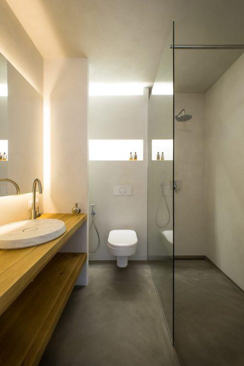 Badkamer met mooi balans van betonstuc en hout