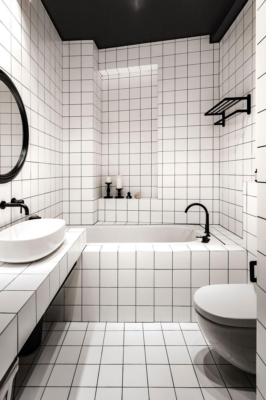 Badkamerontwerp met vierkante witte tegels en een zwart plafond