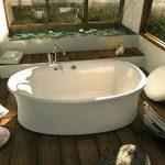 Badkamer met vrijstaand bad en houten vloer