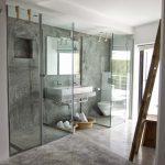 Betonstuc badkamer met twee glazen cabines
