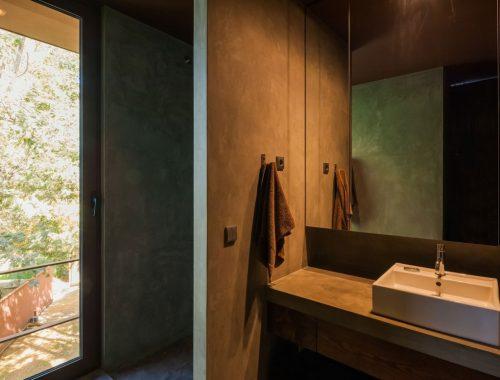 Betonstuc en walnoot hout in badkamer