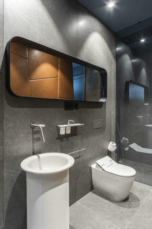 De grote muur in deze stoere badkamer is bekleed met cognac leren wandbekleding!