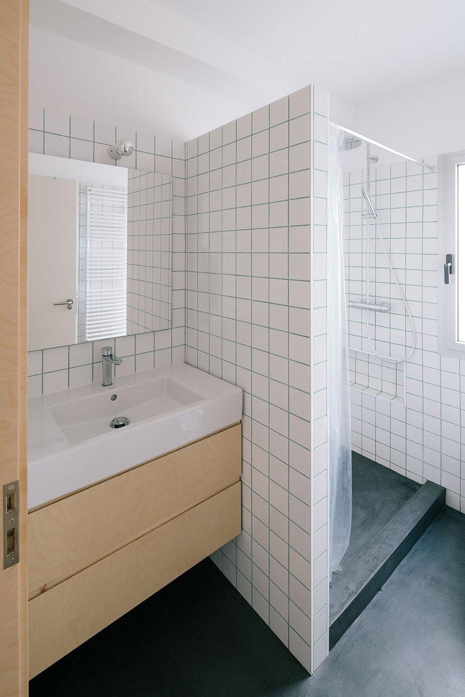 Deze badkamer met een zwarte rubberen vloer
