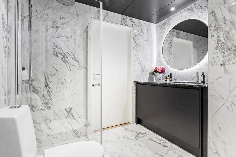 Deze chique badkamer heeft een strak en zwart plafond gekregen
