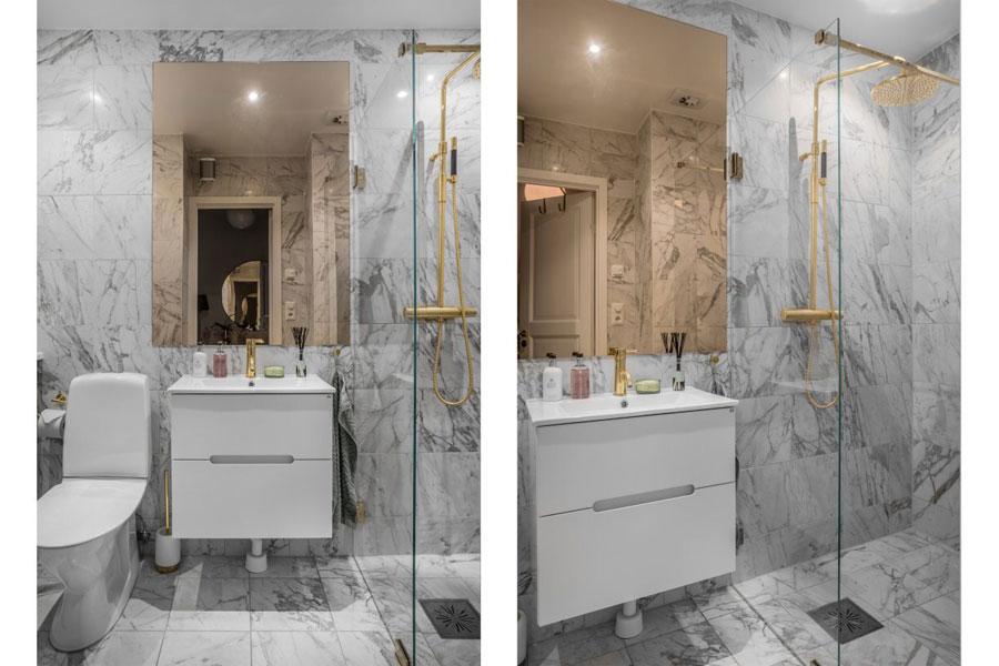 Deze kleine badkamer is erg chic ingericht met marmeren tegels en gouden accenten
