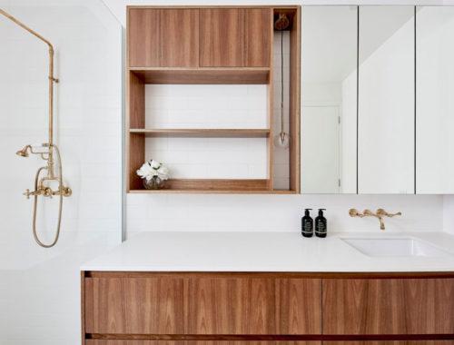 Deze kleine badkamer is super leuk ingericht met patroontegels en houten meubel