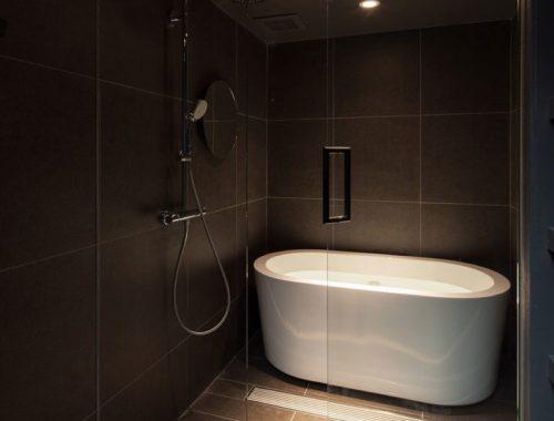 Donkere badkamer met een glazen wand en deur