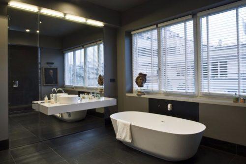 Grote grijze badkamer door Mood Works