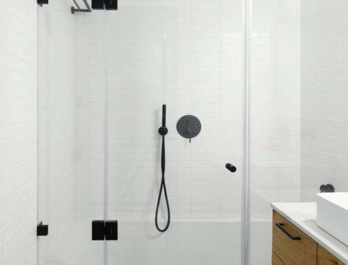 In deze kleine stoere badkamer vind je een mooie bad-douche-combinatie!