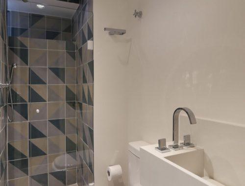Kleine badkamer met betonstuc en patroontegels