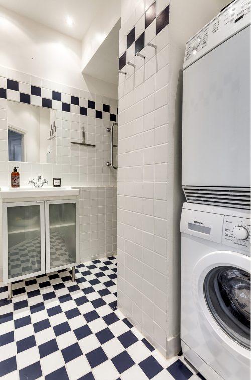 Kleine l-vormige badkamer met wasmachine en droger