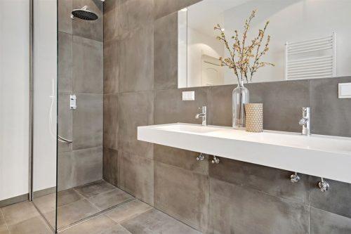 Minimalistische badkamer met betonlook tegels - Badkamers voorbeelden