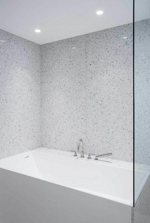 Minimalistische badkamer met gespikkelde witte tegels