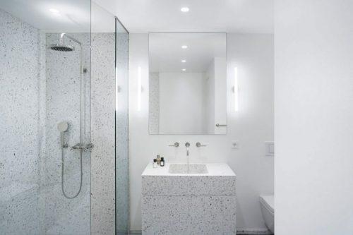 Minimalistische badkamer met gespikkelde witte tegels - Badkamers ...