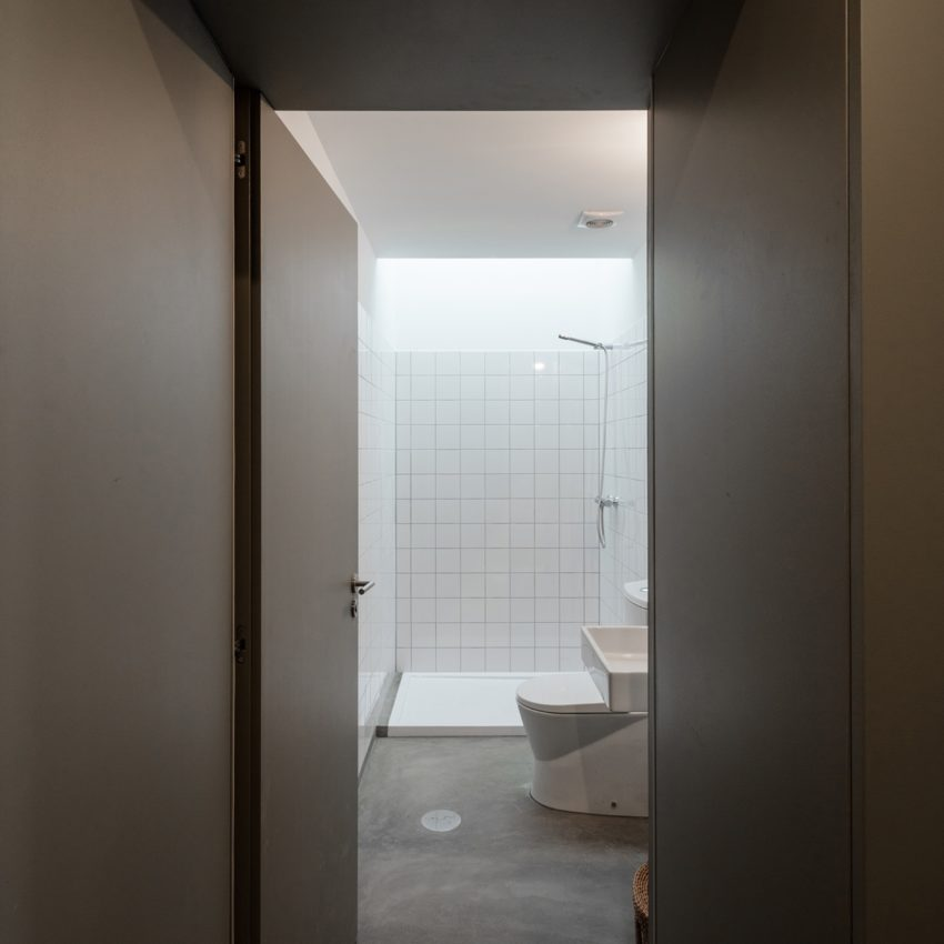 Minimalistische kleine badkamer met betonlook vloer en witte wandtegels