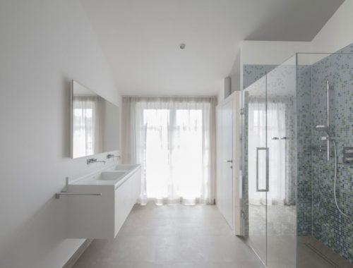 Moderne badkamer met grote glazen wand en glazen deur
