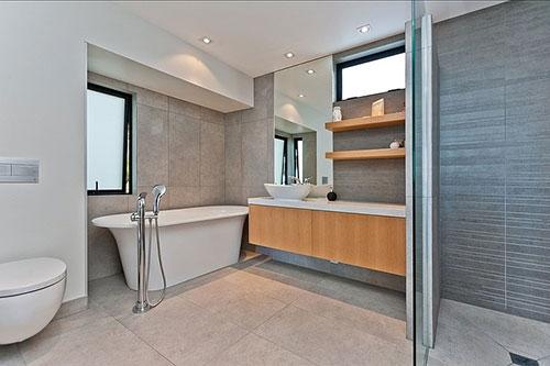 Moderne badkamer met vrijstaand bad tegen de muur