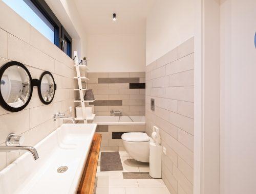Smalle lange badkamer met lichtgrijze tegels