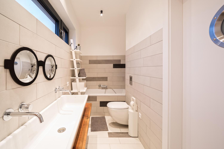 Smalle lange badkamer met lichtgrijze tegels - Badkamers voorbeelden