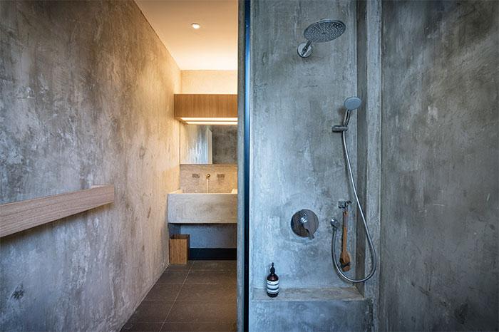 strakke-betonstuc-badkamer-met-houten-accenten