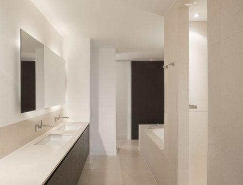 Strakke witte badkamer met langwerpige badmeubel
