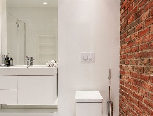 Witte badkamer met bakstenen muur