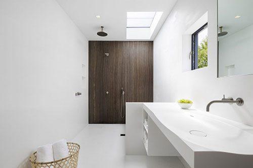 Witte badkamer met donkerbruine houten muur